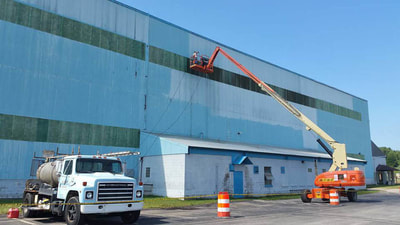 large factory building being painted using scaffold lift