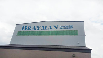 large factory building signage being painted