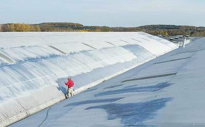man painting a warehouse metal roof