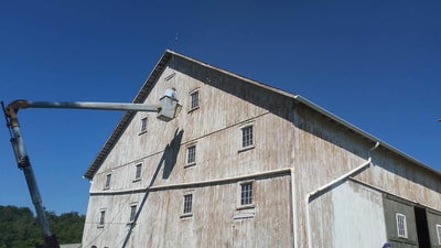 old barn being painted from a bucket truck lift