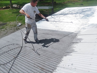 man painting large metal roof