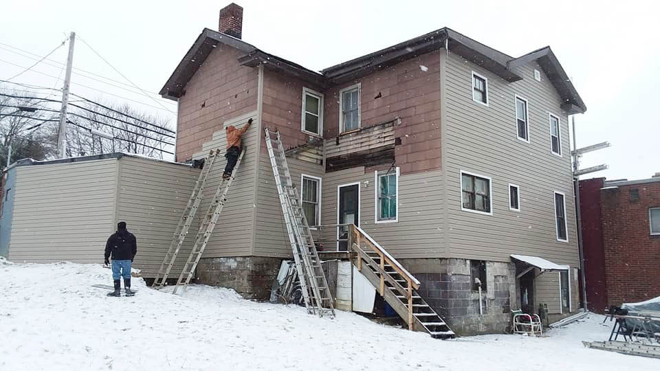 workers installing siding on a house during winter