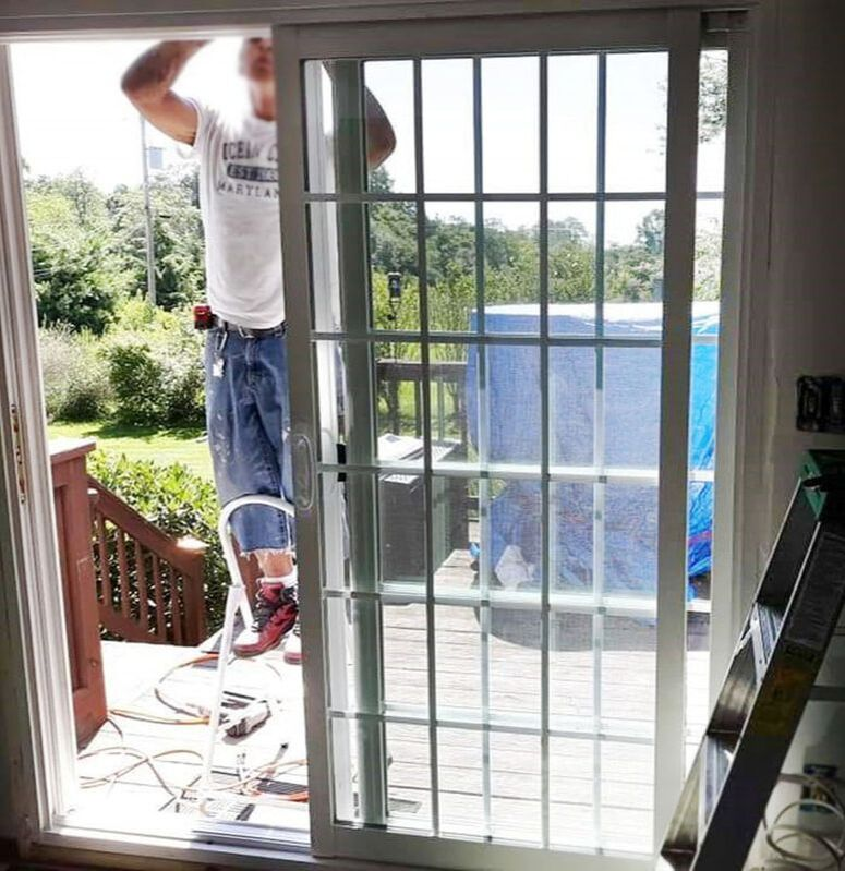 worker installing sliding glass door to patio deck